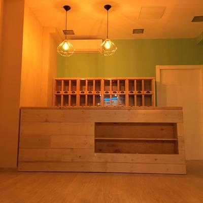 Mostrador de madera natural, suelo y puerta de herbolario.
