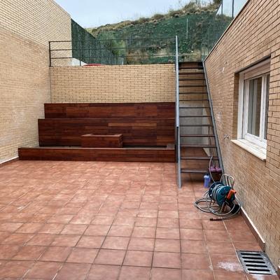 Patio con jardineras, suelo y escalera de forja