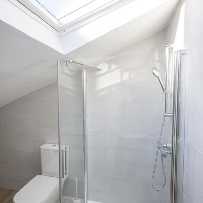 Baño con ventana en techo en buhardilla