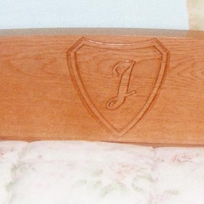 Cabecero de cama con inicial tallada