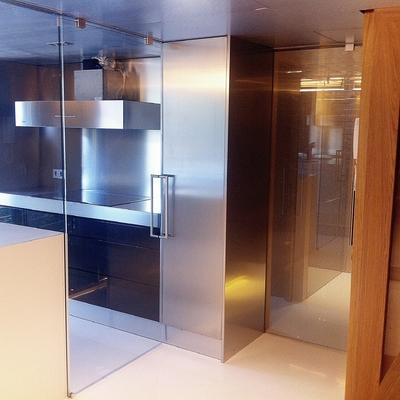 Cocina americana con paneles y puertas de cristal securit
