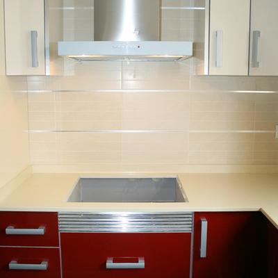 Detalle frente cocina zona coccion con mobiliario lacado en rojo