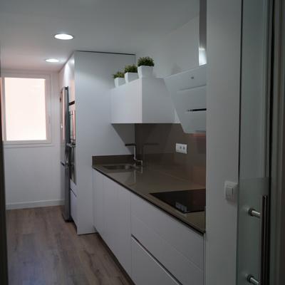 Cocina blanca suelo tarima y puerta de cristal