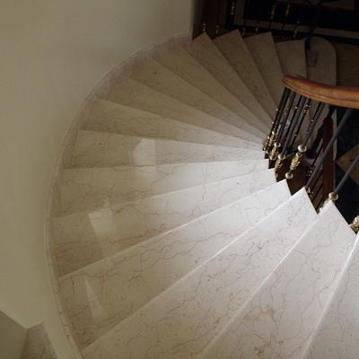 Escalera de caracol , revestida con marmol Crema Quevedo .