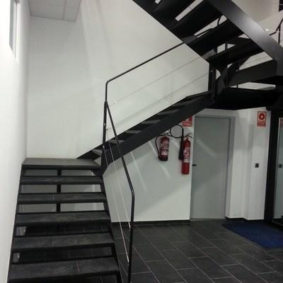 escaleras en hierro con pasos porcelánicos y barandilla en cables de acero