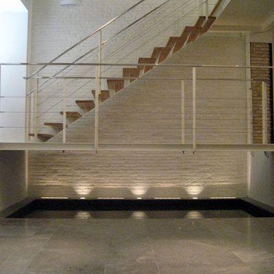 Escalera metalica colgada sobre lamina de agua