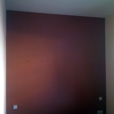 fondo en pared color rojo fuego destacando con el resto en beige en entrada de vivienda