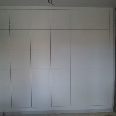 Armario lacado en blanco con puertas abatibles.