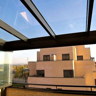 Instalación de techo fijo con estructura completa de soporte y vidrio transparente con control solar y cortinas de cristal como cerramiento vertical.
