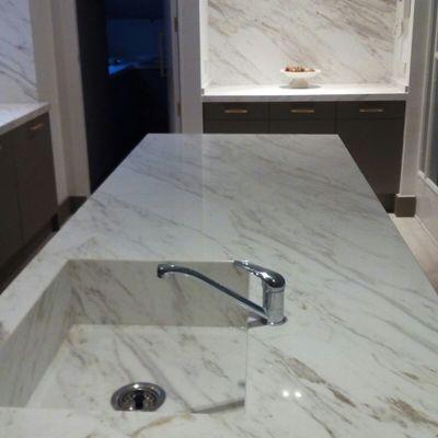 Isla en marmol Volakas diagonal con lavabo integrado