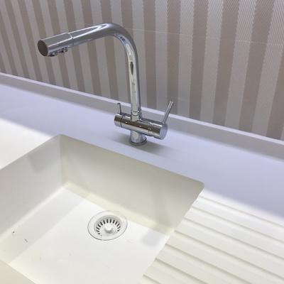 Encimera y lavamanos de Krion by PORCELANOSA y grifo doble con filtro de ósmosis inversa