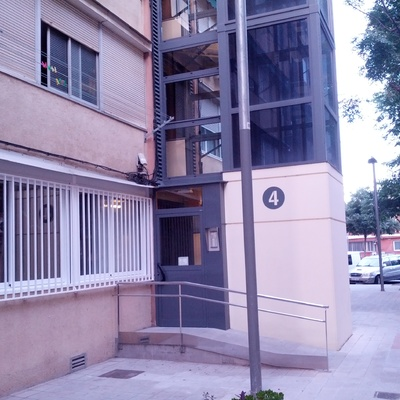Instalación de ventanas correderas y rejas metálicas en un piso bajo.