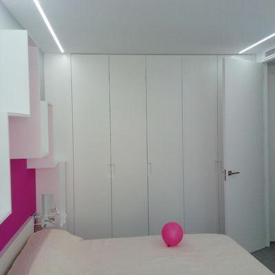 Armario y puertas de suelo a techo lacados en blanco.