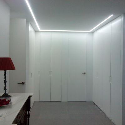 Iluminación de led y armarios y panelado lacados en blanco.