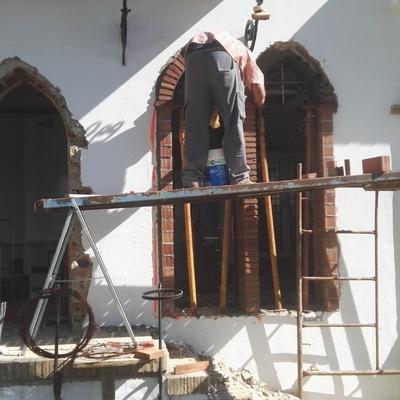 Apertura de huecos  con arcos apuntados en muro de hormigón para puertas y ventanal
