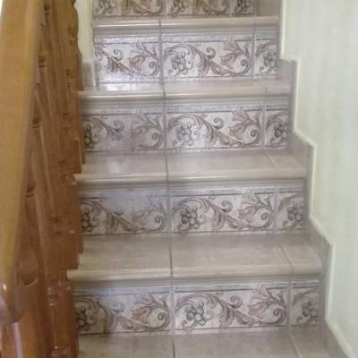 Escalera con peldaños y tabica con cenefa decorativa