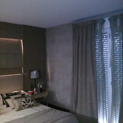 ventanal cubierto con cortinaje a juego con el cabecero