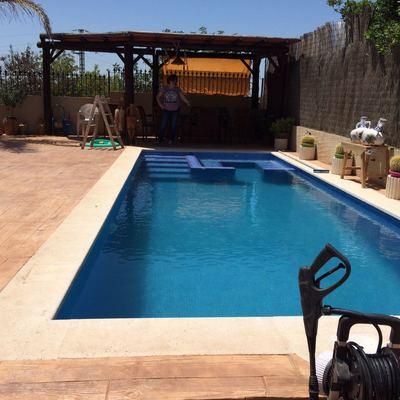 piscina de hormgión con zona spá y terraza con hormigón impreso madera