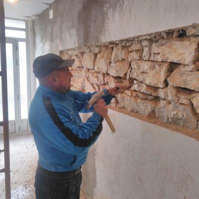 Picar el mortero hasta la piedra en una casa y rejuntar la piedra