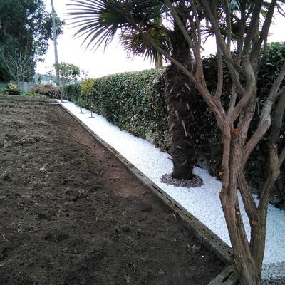 Recubrimiento de jardinera con canto rodado blanco y piedra volcánica.