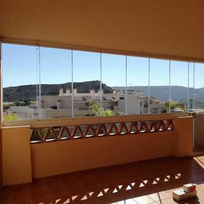 Terraza cerrada con cortinas de cristal y puerta con cerradura