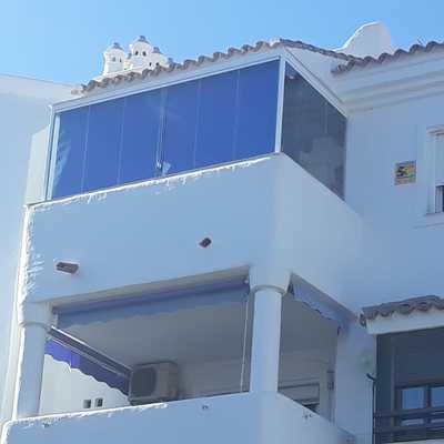 Balcón cerrado con cortinas de cristal