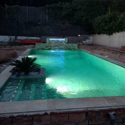 Foto nocturna de piscina privada con jardinera interior y cascada.