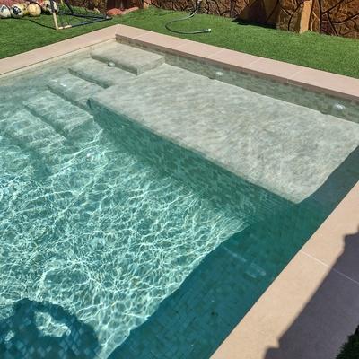 Piscina con coronación porcelánica beige y gresite Hisbalit Aqualuxe Mallorca en formato 4x4.