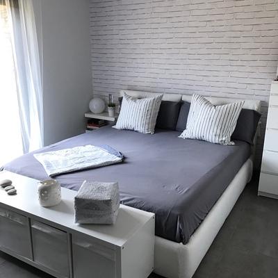 Habitación principal con pared de ladrillo