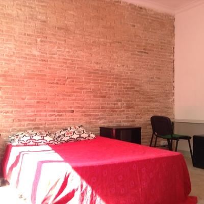 Habitación reformada con pared obra vista
