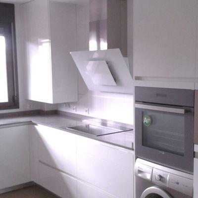 Zona de cocción, con campana en cristal blanco.