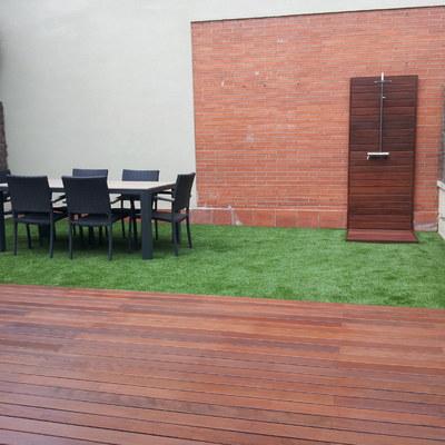 Jardín con césped artificial, madera tropical y ducha de jardín