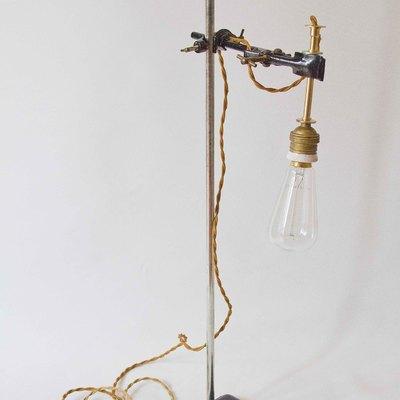 Original lámpara vintage realizada con tripode de los años `50. El casquillo es cerámico e incluye una bombilla incandescente. Cuenta con un regulador para el encendido y apagado. Lleva enchufe.