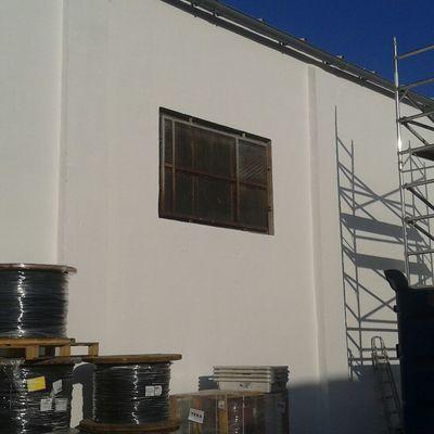 Reparación y pintado de paredes naves industriales con andamiaje.