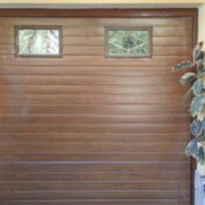 Puerta seccional en imitacion madera con visores en rombo
