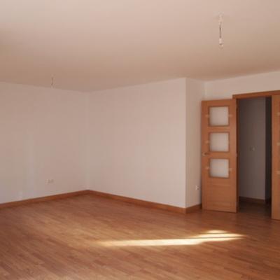 Salón con paredes lisas, suelo de tarima y puertas de pino