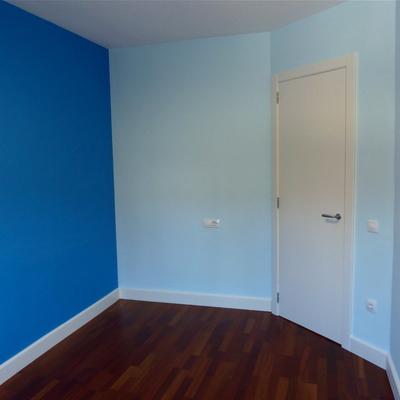 Habitació infantil pintada amb dos tons de blau i la porta i sòcols lacats amb Sikken satura blanc.