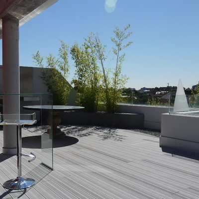Terraza madera tecnológica y jardinera lacada