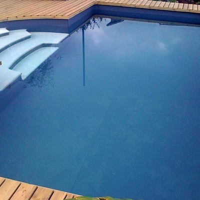 Piscina azul marino con escalera blanca antideslizante
