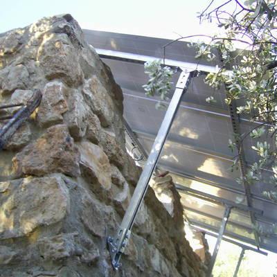 marquesina en vivienda unifamiliar anclada a muro piedra