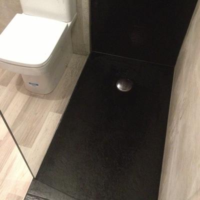 Plato ducha pizarra color negro con mampara fija y alicatados a juego.