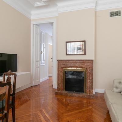 Habitación con parqué de madera natural y chimenea de mármol