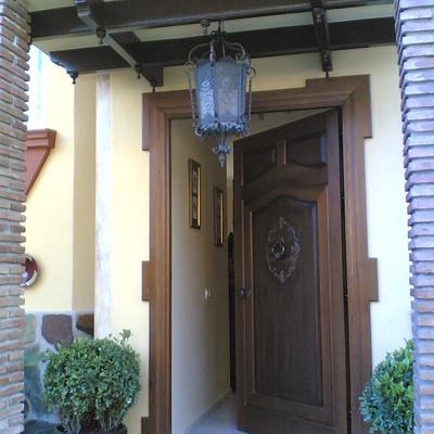 Puerta de entrada con talla y artesonado en techo.