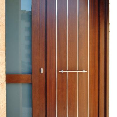 Puerta de exterior con listelos de acero inox.