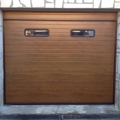Puerta seccional acanalada imitación madera clara con ventanas.