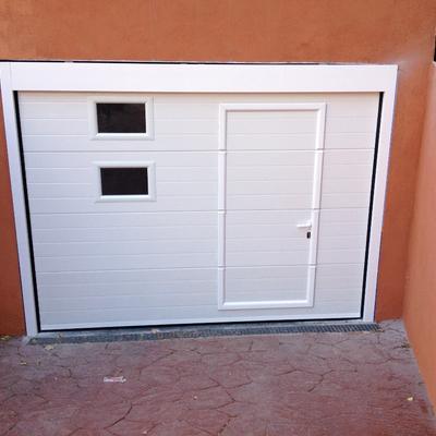 Puerta seccional blanca con peatonal incorporada y ventanas