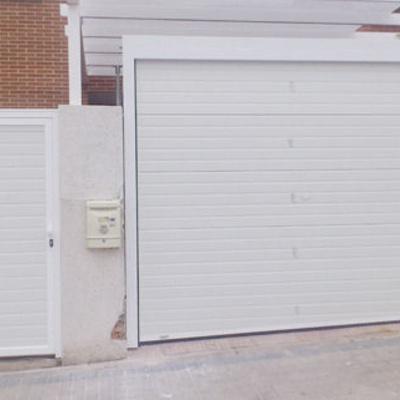 Puerta seccional Acanalada blanca con peatonal al lado panelada