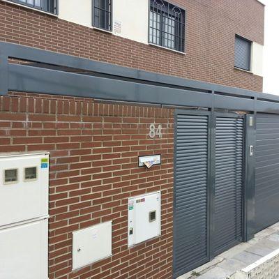 Frontal de vivienda con puerta seccional, techo acristalado y puerta peatonal de lama eliptica