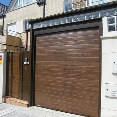 Puerta seccional imitacion madera con peatonal panelada de hierro