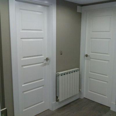 puertas de cuarterones lacadas blanco roto con plintos y rodapie altos